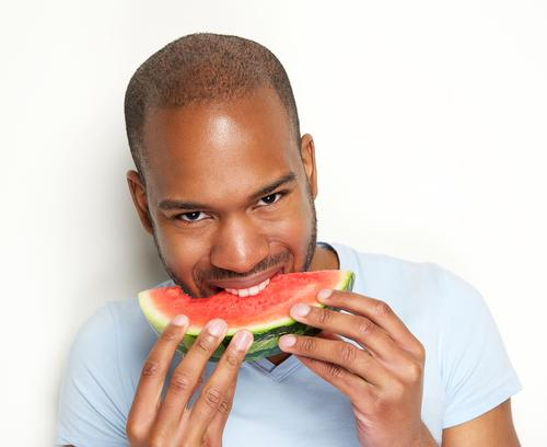 Man smiling and eating watermelon