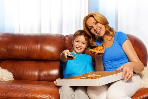 Kid and mother eating pizza while watching TV
