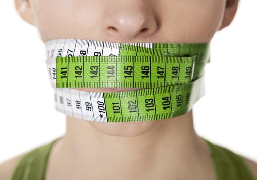 Woman with measuring tape over mouth