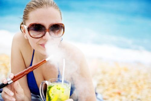 Woman on beach smoking hookah