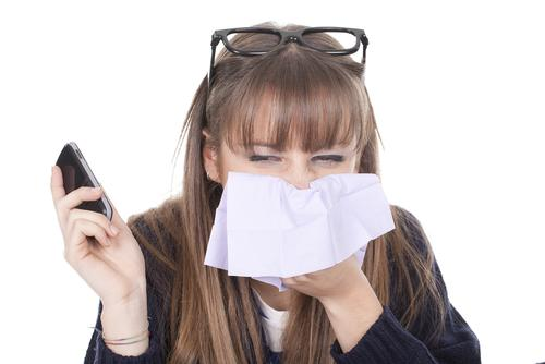Woman holding cellphone and sneezing