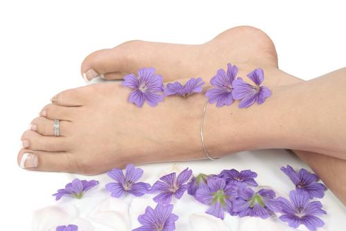 womans-feet-crossing-each-other-purple-flowers-sides