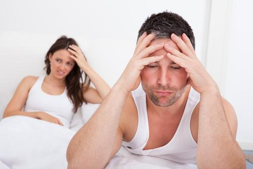 Frustrated man sitting on bed in front of woman