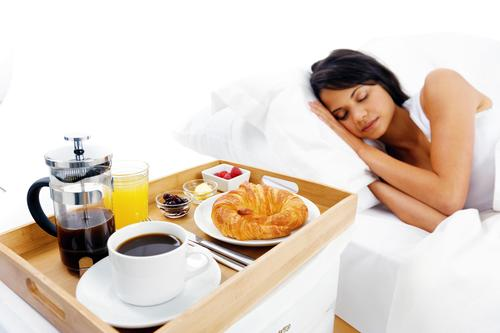 Woman sleeping next to breakfast cart