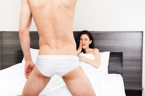 Woman laughing at man in the bedroom