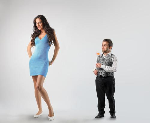 Short man paying court to tall woman