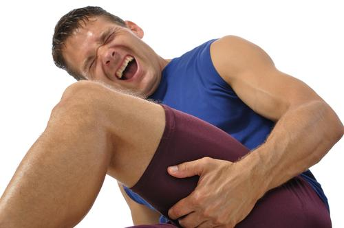 Male athlete clutching his hamstring in excruciating pain