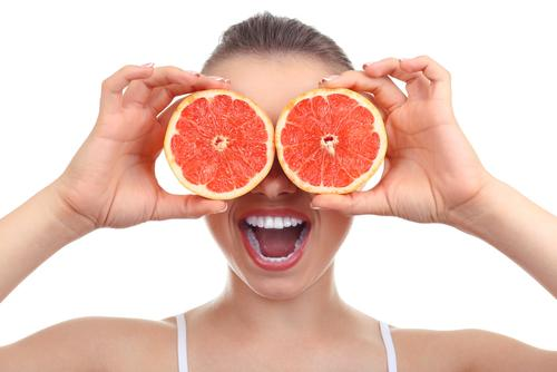 Girl with grapefruit covering eyes