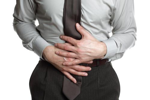 Businessman holding his stomach in pain