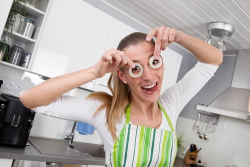 Young woman posing with onion rings in the kitchen