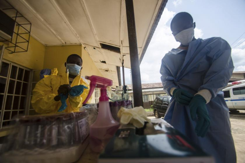 Medical staff puts protective gear in Kenema government hospital before taking a sample from a suspected Ebola patient