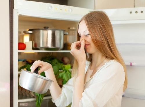 Woman hold nose and cooking pot because of bad smell