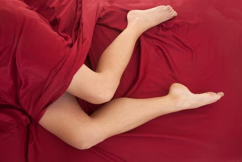Legs of woman on red sheet