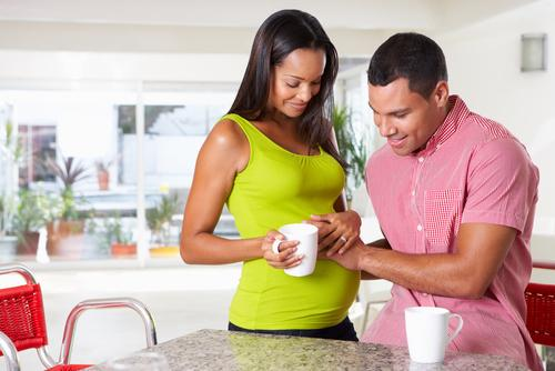 Pregnant woman and husband having breakfast in the kitchen
