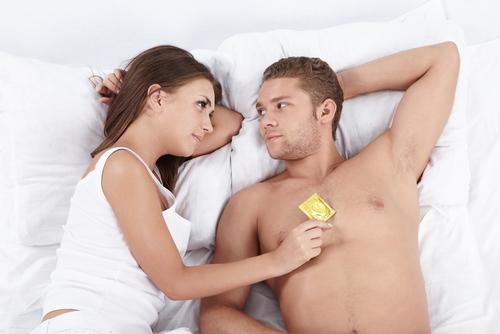 Couple in bed with condom