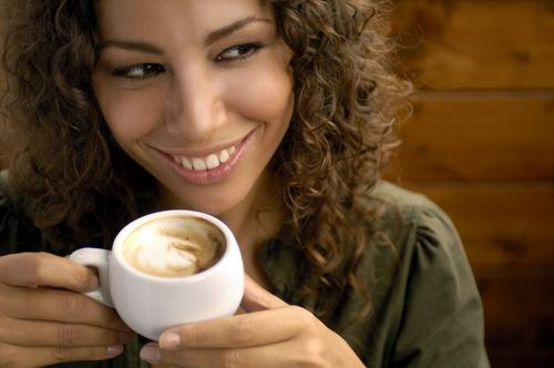 Woman smiling drinking cappuccino