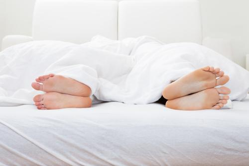 Couples' feet in bed+