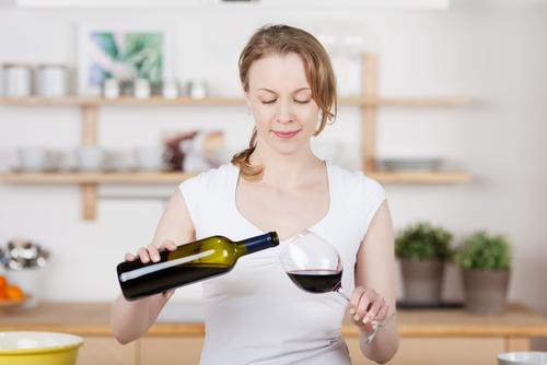 Woman pouring herself a glass of wine in the kitchen
