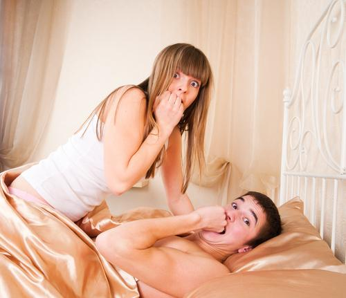 Surprised couple lying in bed