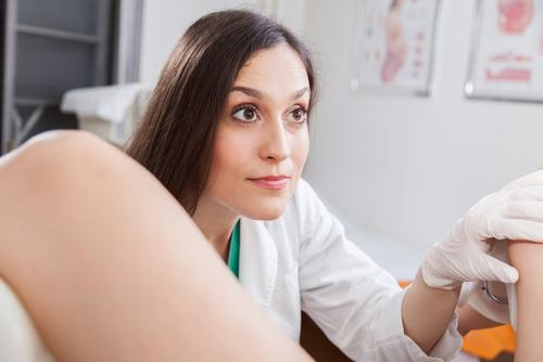 Female gynecologist looking up at patient