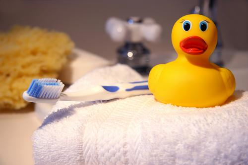 ubber duck, toothbrush and sponge on bathroom counter
