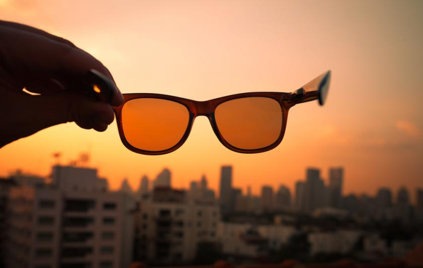 Orange glasses held up to sky