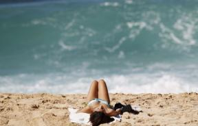 woman sunbathes at beach in Hawaii