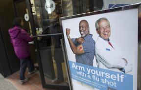 People enter a pharmacy next to a sign promoting flu shots in New York