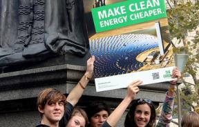 Teenagers holding sign: Make clean energy cheaper - Melbourne World Environment Day 2011