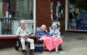 Seniors sitting in front of store