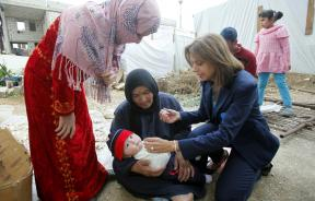a health worker vaccinates Syrian child