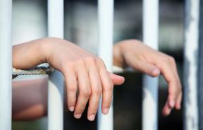 Hands of inmate behind bars
