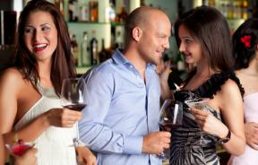 Man and woman talking to each other at crowded bar