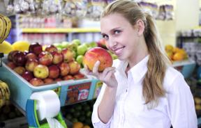 Woman smelling mango at the supermarket