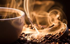 Big aroma of coffee from cup next to coffee beans