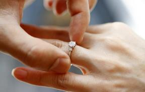 A man puts an engagement ring on a woman's finger.