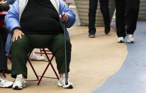 An obese woman sits on a chair.