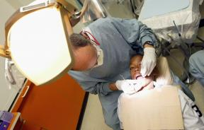 A dentist performs a dental examination on a young boy.