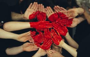 Hands with red paint forming heart