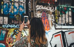 Woman taking pic of graffiti